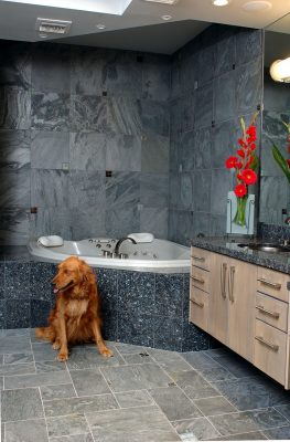 Jetted corner tub set into Blue Pearl granite with Ostrich blue slate, metal and glass tile mosaic walls make 'Doggie' happy!