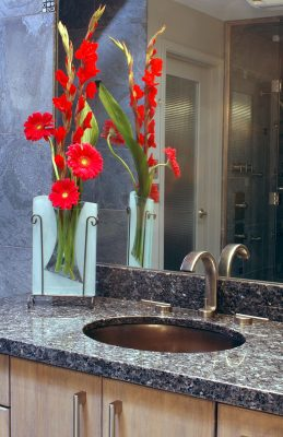 This simple under mount polished graphite ceramic sink and contemporary brushed nickel handles and faucet are as sleek as the Blue Pearl granite slab counter.