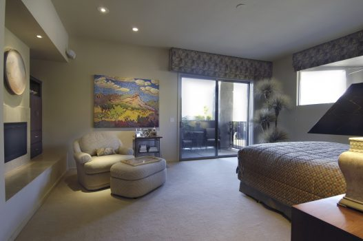The art inspires this contemporary master bedroom.  Fireplace and TV have clean finishes.