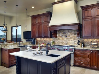 Features wood trimmed custom vent hood with corbels, contrasting painted black island.