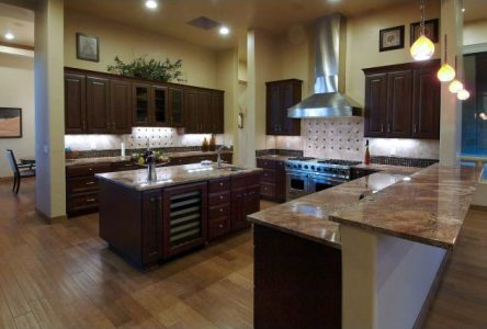 Dark walnut cabinets contrast with the lighter wood plank floor and Juperana Florence granite make for a dramatic masculine kitchen.