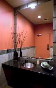 Elements are brightly colored chili pepper wall paint, Black Galaxy Granite free floating vanity with under counter stainless steel lav.  Mirror is framed with accents of glass tile.