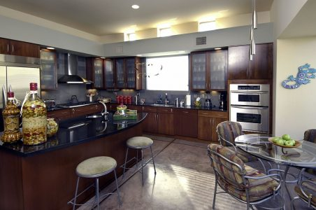 Stainless steel pendant lights and stainless steel vent hood and appliances are a bright touch with the frosted glass cabinet fronts.