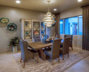 Dining Room - Spiral chandelier ties in well with the area rug and decorative metal on the Breakfront Cabinet. Eye candy on the wall in blown glass.