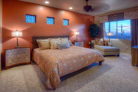 The desired result was a balance between color and texture with the Arizona Clay wall paint, geometric print bedding, wood, linen and nailhead night stand. The small windows were enhanced with a Bronze colored Tableaux geometric overlay that was also used in the Cornice box to tie the whole presentation together.