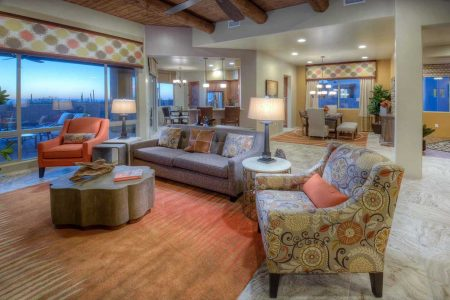 "Model Home Living Space with a beautiful view out to the patio and desert sunset beyond. We didn't want to distract from the views. The fireplace has elegant travertine 12"" x 24"" stone tiles alternating with rows of Ancient Wave Tile, and the surround is entirely composed of the Ancient Wave Tile. The colorful area rug ties the setting all together."